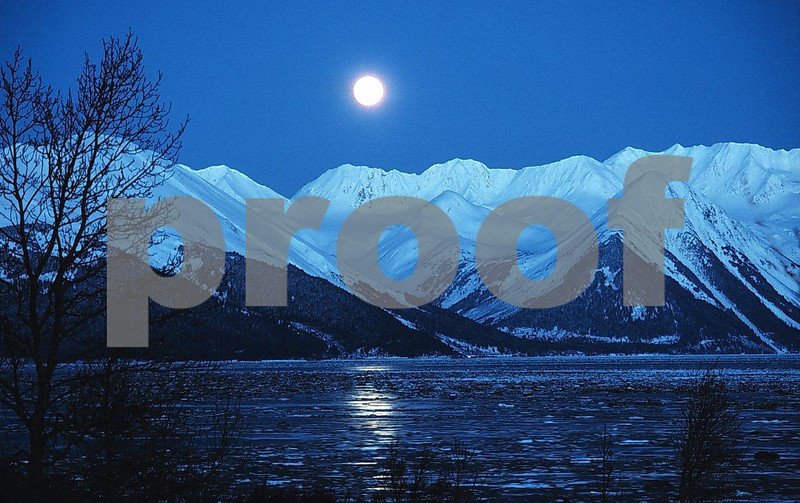 AK Turnagain Arm: On a very cold winter day, a full moon rises over Turnagain Arm in Cook Inlet southeast of Anchorage, Alaska.
