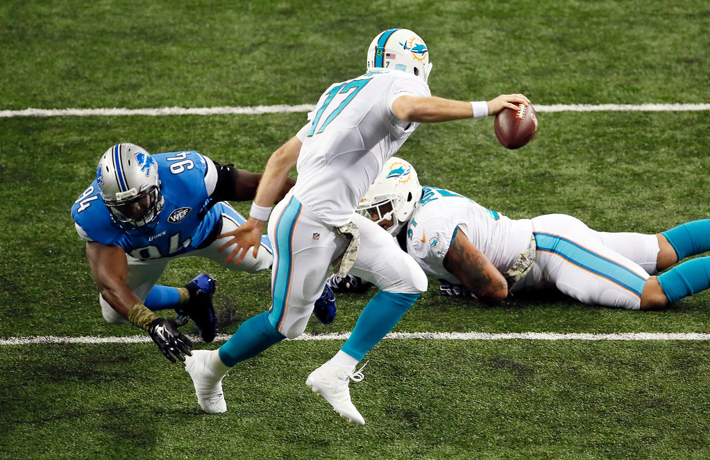 . Detroit Lions defensive end Ezekiel Ansah (94) breaks through the line to sack Miami Dolphins quarterback Ryan Tannehill (17) during the first half of an NFL football game in Detroit, Sunday, Nov. 9, 2014. (AP Photo/Paul Sancya)