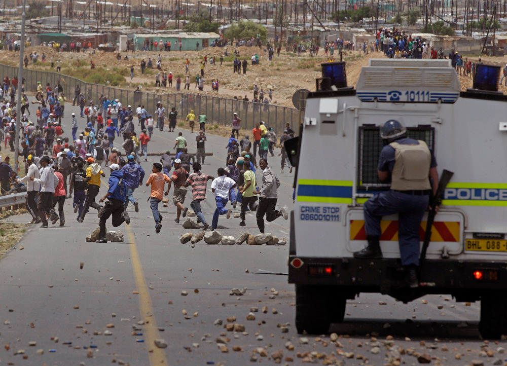 Description of . Striking farm workers, run away from South African police, as they demonstrate in De Doorns, South Africa, Thursday, Jan 10, 2013. Striking farm workers in South Africa have clashed with police for a second day during protests for higher wages. The South African Press Association says police on Thursday fired rubber bullets at rock-throwing demonstrators in the town of De Doorns in Western Cape province, and protests were occurring in at least two other towns. (AP Photo/Schalk van Zuydam)