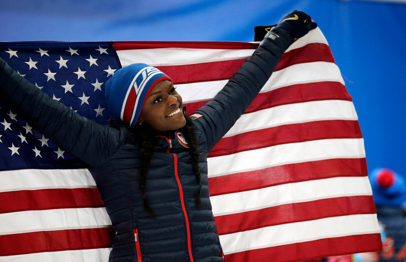 . Bronze medal winner from the United States Aja Evans holds the flag after the women\'s bobsled competition at the 2014 Winter Olympics, Wednesday, Feb. 19, 2014, in Krasnaya Polyana, Russia.(AP Photo/Jae C. Hong)