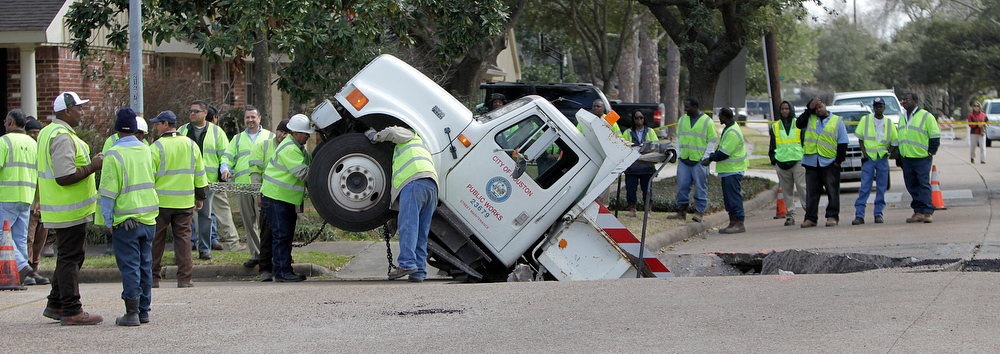 . City crews work to attach chains on a City of Houston Public Works dump truck, after it fell into a sink hole caused by a cave-in on Balmforth at Dumfries near Godwin Park, Tuesday, Feb. 8, 2011, in Houston. Officials said the truck was carrying gravel to repair potholes on the street when the road fell out beneath the truck, which fell into the hole backwards. No injuries were reported and the truck was later lifted out by a large crane. (AP Photo/Houston Chronicle, Karen Warren)