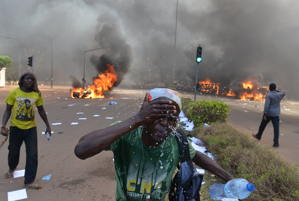 . A protester rince his face outside the parliament in Ouagadougou on October 30, 2014 as cars and documents burn outside. ISSOUF SANOGO/AFP/Getty Images