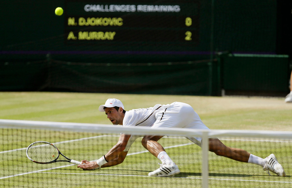 . Novak Djokovic of Serbia plays a return to Andy Murray of Britain during the Men\'s singles final match at the All England Lawn Tennis Championships in Wimbledon, London, Sunday, July 7, 2013. (AP Photo/Alastair Grant)