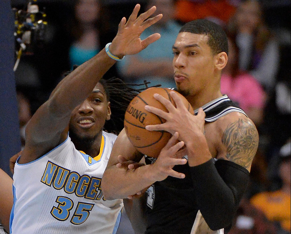 . San Antonio Spurs shooting guard Danny Green (4) hauls down a rebound from Denver Nuggets small forward Kenneth Faried (35) during the first quarter October 14, 2013 at Pepsi Center. (Photo By John Leyba/The Denver Post)