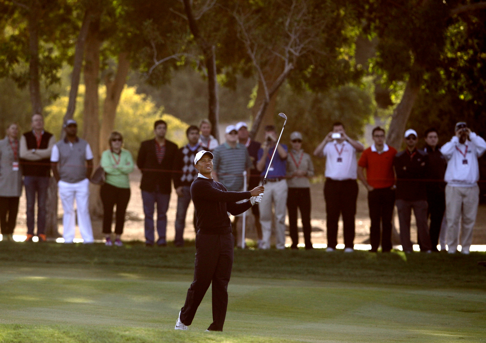 Description of . Tiger Woods from U.S. follows his ball on the 12th hole during the first round of Abu Dhabi Golf Championship in Abu Dhabi, United Arab Emirates, Thursday, Jan. 17, 2013. (AP Photo/Kamran Jebreili)