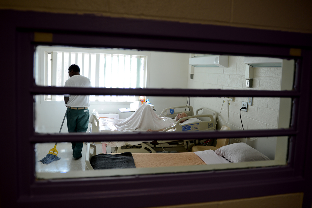. Wayne Rose, left, mops the floor in Robert Bryan\'s room as he lies in bed waiting to die behind the prison walls of Colorado Territorial Correctional Facility, November 08, 2012. Rose, a fellow prisoner, works seven days a week in the prison\'s infirmary taking care of Bryan and other hospice patients in the prison\'s hospice program. (Photo By RJ Sangosti/The Denver Post)