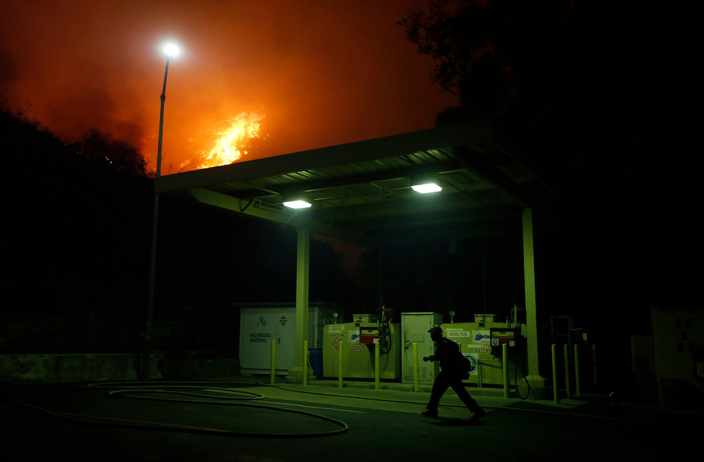 . A firefighter pulls along a hose as he battles to protect a CalTrans Maintenance Station and Fuel Depot from the Springs Fire near Pacific Coast Highway and the Los Angeles County Line at Malibu, California, May 2, 2013. REUTERS/Patrick T. Fallon