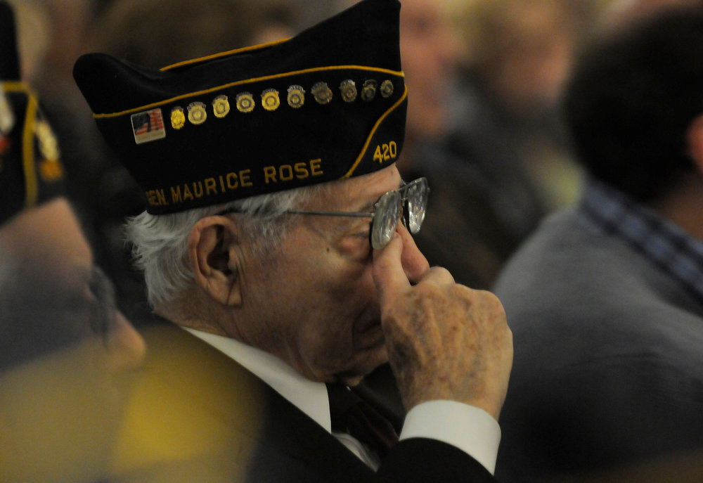 Description of . World War II veteran Hebert Isner of Oak Park, Mich., wipes his eyes during the Yom HaShoah, Holocaust Day of Remembrance at the Holocaust Memorial Center in Farmington Hills, Mich., on Sunday, April 7, 2013.  (AP Photo/Detroit News, Elizabeth Conley)