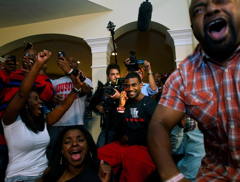 . D.J. Hayden from Houston, center, smiles as he receives a call from the Oakland Raiders telling him he was selected 12th overall in the NFL football draft at his house in Missouri City, Texas. (AP Photo/Houston Chronicle, Cody Duty)