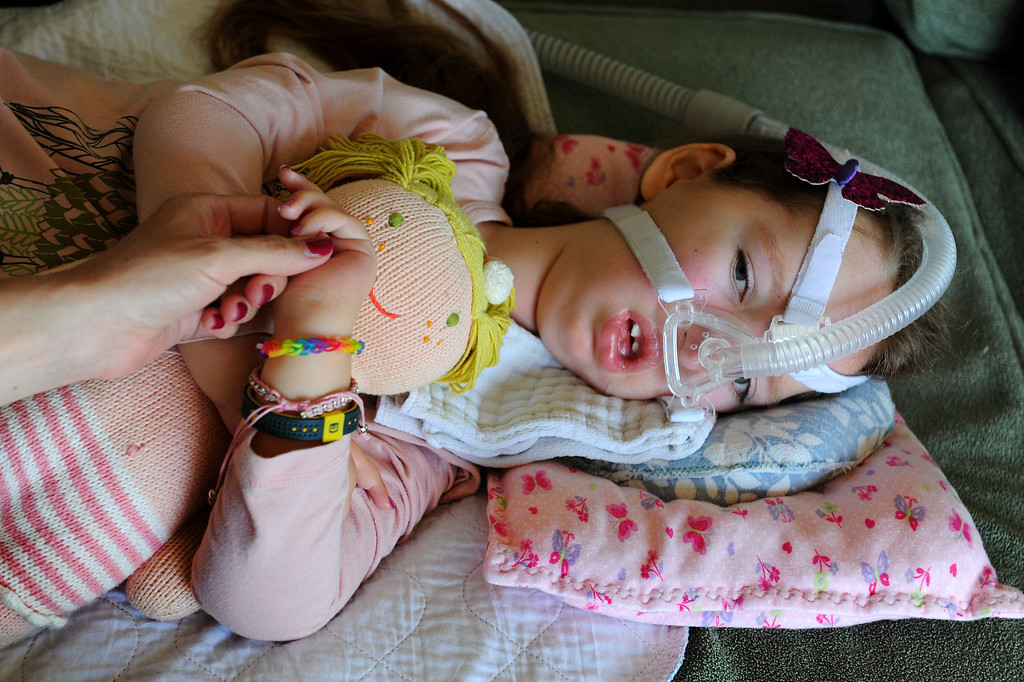 . Gwendolyn Strong lays with her doll on a sofa in their Santa Barbara home. Gwendolyn was born with spinal muscular atrophy. (Photo by Michael Owen Baker/Los Angeles Daily News)