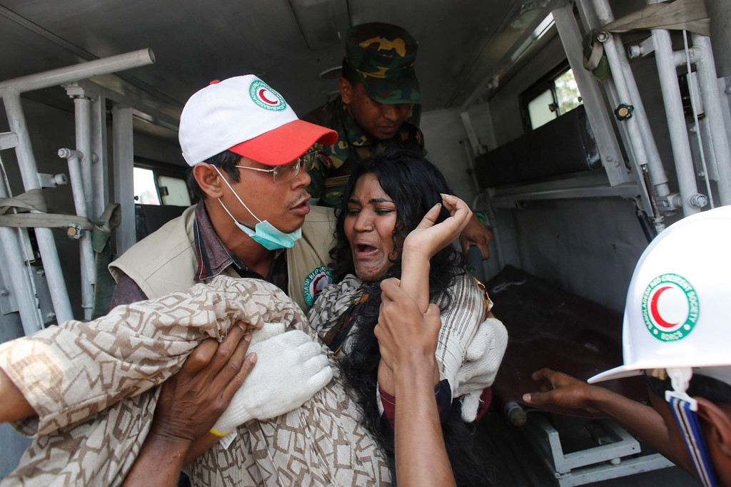 . A rescue worker carries a garment worker to an ambulance after pulling her from the rubble of the collapsed Rana Plaza building in Savar, 30 km (19 miles) outside Dhaka April 24, 2013.  REUTERS/Andrew Biraj
