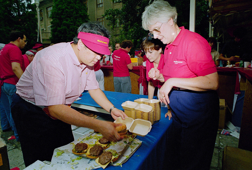 ". Volunteers Betty Halsey, far right, and Jeanie Roberts, wait impatiently as McDonald\'s ""Big Macs\"" are boxed up at the U.S.. embassy in Beijing during a party celebrating American Independence Day, Wednesday, July 4, 1990. The burgers, and the McDonald\'s workers, were flown in from Hong Kong for the occasion. (AP Photo/Mark Avary)"