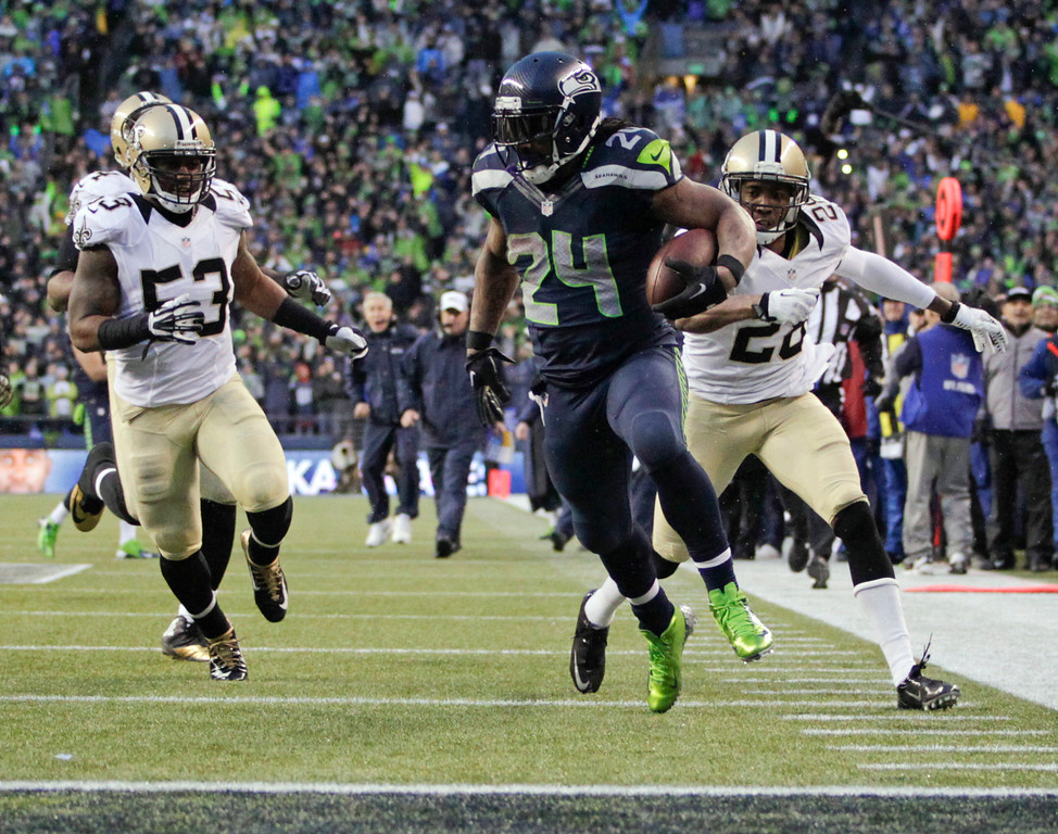 . Seattle Seahawks running back Marshawn Lynch (24) runs past New Orleans Saints cornerback Keenan Lewis (28) and outside linebacker Ramon Humber (53) to score a 31-yard touchdown during the fourth quarter of an NFC divisional playoff NFL football game in Seattle, Saturday, Jan. 11, 2014. (AP Photo/John Froschauer)