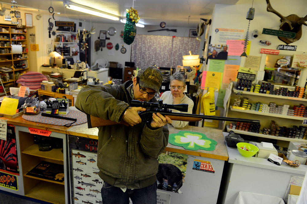 Description of . WALSENBURG, CO - FEBRUARY 26: Howllowpoint Gun Shop Owner Erin Jerant looks on as Justin Noga checks the scope mount in Walsenburg. Jerant says she has known Noga since he was young enough to sit on the store's countertops and has been servicing his guns for just as long. Many gun owners in southern Colorado agree that responsible ownership and operation of guns begins at home. The photo is funny to me in the sense that it is a nice juxtaposition of what one might expect of gun ownership in Noga and what one likely does not expect in Jerant. Jerant's shop was full of the essential gun shop equipment with some quirks -- knit work, cats, candy and the homey feel of grandma's house. That is not, however, to imply that Jerant wasn't packin' as she had many decals letting potential intruders know that she was strapped and ready. (Photo by AAron Ontiveroz/The Denver Post)