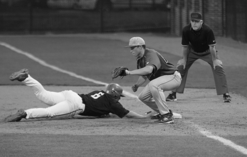 #6 Aaron Miller slides into first base as the UNC-Asheville pitcher attempts to throw him out.