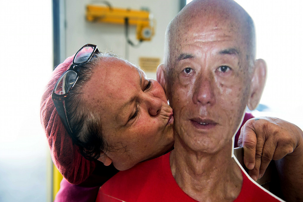 . Monica Lopez, 53, of Irwindale, kisses a cardboard cutout of Huy Fong CEO David Tran during the chili grinding process tour at Huy Fong Foods in Irwindale on Friday, August 22, 2014. (Photo by Watchara Phomicinda/ Pasadena Star-News)