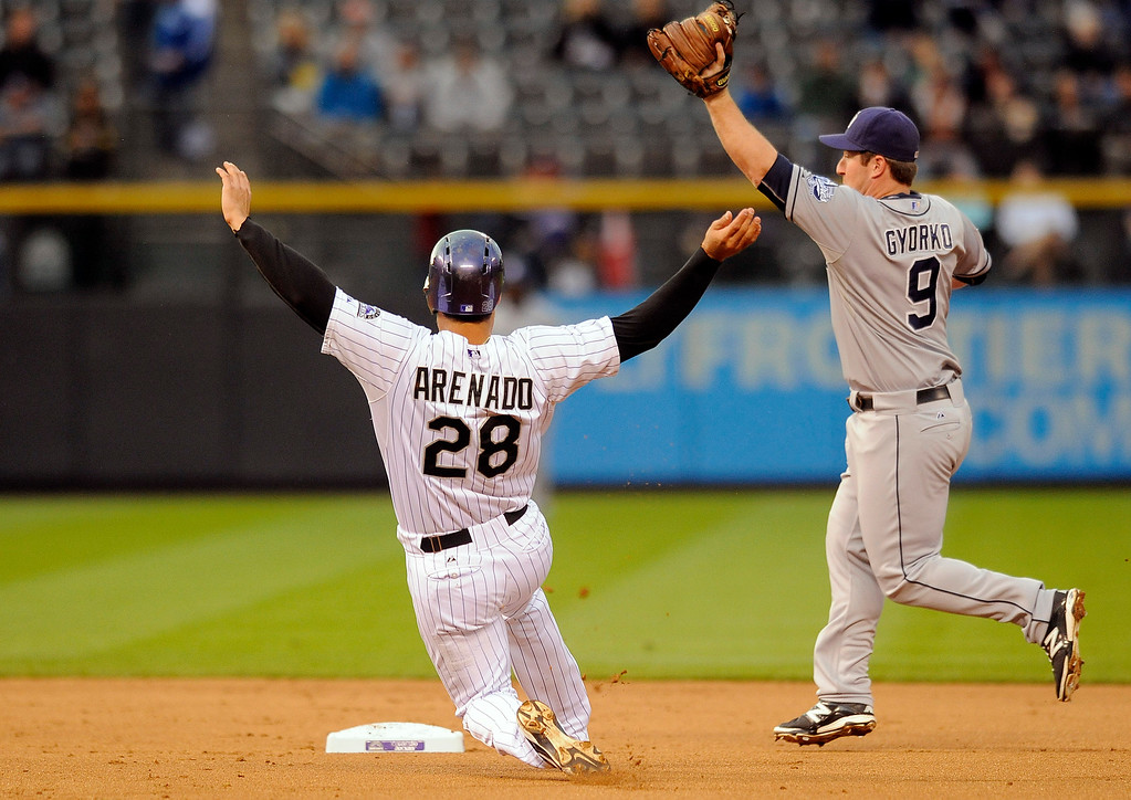 . Colorado Rockie\' Nolan Arenado is forced out at second base by San Diego Padres second baseman Jedd Gyorko in the first inning of a baseball game Friday, Sept. 5, 2014, in Denver. (AP Photo/Chris Schneider)