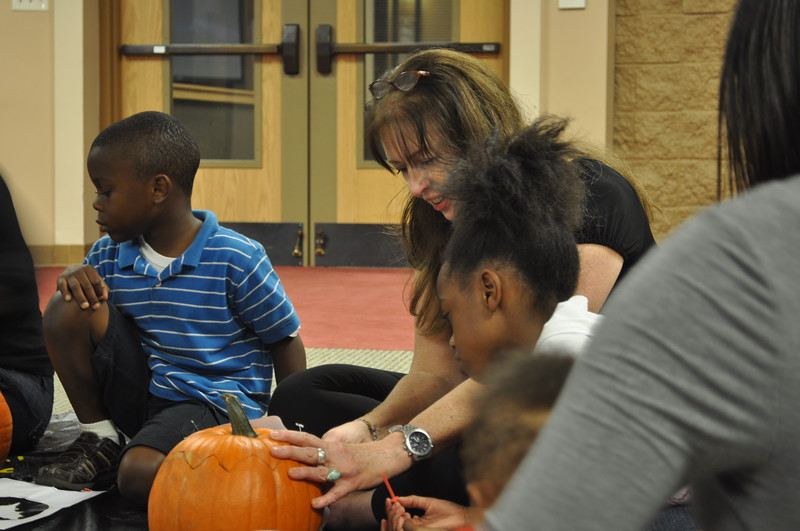 Ms_ Dona guides a young pumpkin carver.jpg