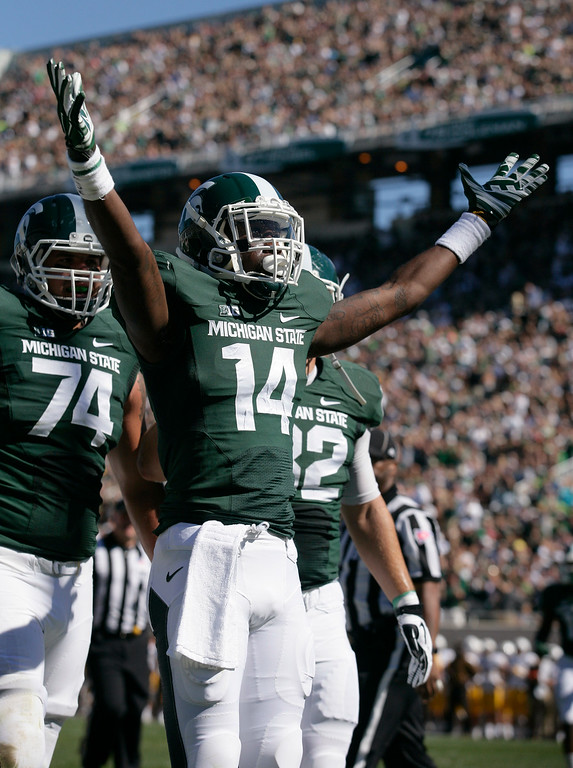 . Michigan State\'s Tony Lippett (14) celebrates his touchdown reception against Wyoming as teammates Jack Conklin (74) and Josiah Price, right, move in to join him during the first quarter of an NCAA college football game, Saturday, Sept. 27, 2014, in East Lansing, Mich. (AP Photo/Al Goldis)