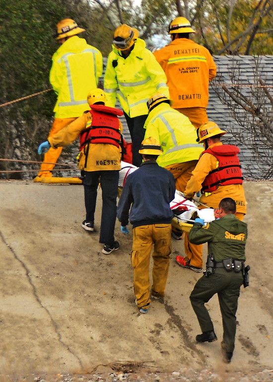 . Firefighters carry the body of a possible victim killed in a storm  Friday, Dec. 12, 2014, in Santa Clarita, Calif. A dangerous storm system that clobbered the Bay Area has pushed into Southern California, causing mudslides and evacuations.  (AP Photo/The Santa Clarita Valley Signal, Katharine Lotze)