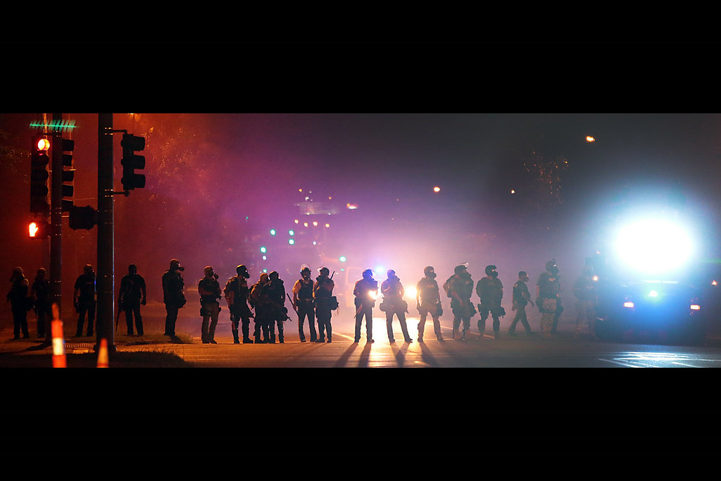 . Police officers work their way north on West Florissant Avenue in Ferguson, Mo., clearing the road of people Wednesday, Aug. 13, 2014.  (AP Photo/St. Louis Post-Dispatch, Robert Cohen)