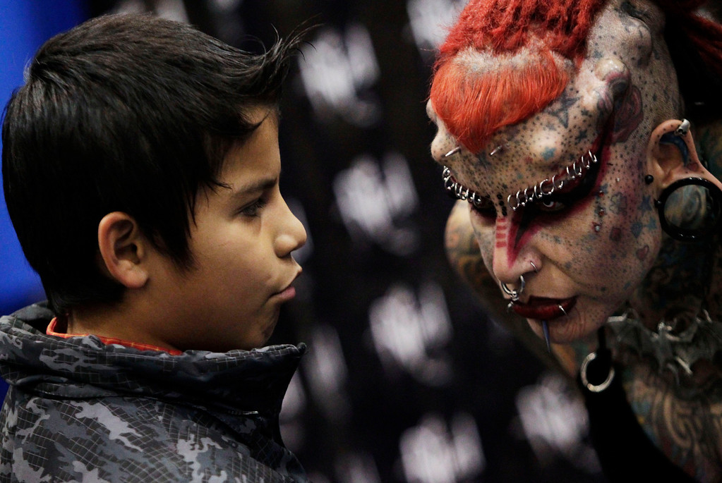 ". Maria Jose Cristerna, a Mexican tattoo artist and former lawyer known as ""Mujer Vampiro\"" (or Vampire Woman), speaks with a boy during the \""Expo Tatuaje\"" international in Monterrey March 2, 2013. REUTERS/Daniel Becerril"