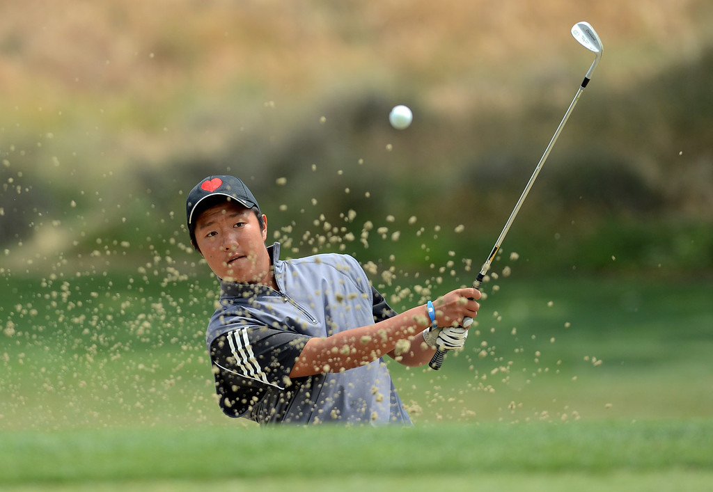 . Hart High School\'s Glen Lee hits a shot out of a bunker while competing in the final round of the Foothill League Newhall Cup golf tournament at TPC Valencia April 24, 2013.(Andy Holzman/Staff Photographer)
