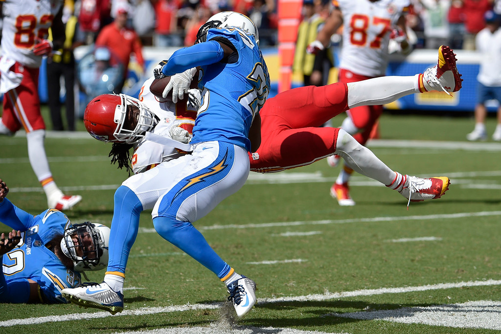. Kansas City Chiefs running back Jamaal Charles (25) is upended by San Diego Chargers cornerback Brandon Flowers while scoring a touchdown during the first half of an NFL football game Sunday, Oct. 19, 2014, in San Diego. (AP Photo/Denis Poroy)