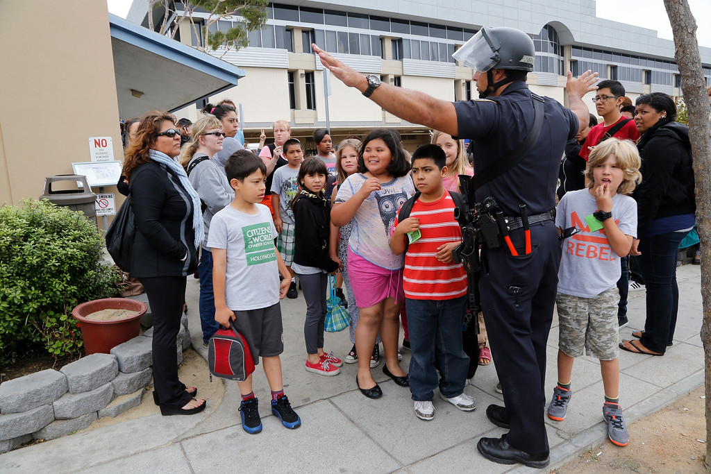. A Santa Monica police officer leads children from Citizens of the World School in Los Angeles out of Santa Monica College, who were there for a planetarium show, as the campus is systematically cleared, in Santa Monica, Calif., Friday, June 7, 2013. Authorities say a gunman carrying an assault-style rifle killed at least six people in Santa Monica before police killed him during a gunfight in the Santa Monica College library.  (AP Photo/Reed Saxon)