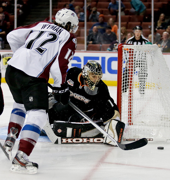 . Anaheim Ducks goalie Jonas Hiller, right, blocks a shot by Colorado Avalanche right wing J.T. Wyman during the first period of an NHL preseason hockey game in Anaheim, Calif., Sunday, Sept. 22, 2013. (AP Photo/Chris Carlson)
