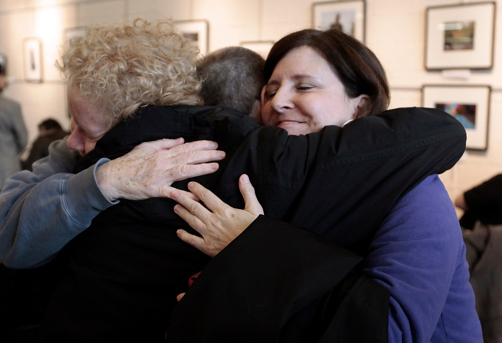 . Susan Horowitz, left, and Judy Valenti, right, hug a friend in Ferndale, Mich., Friday, March 21, 2014. A federal judge has struck down Michigan\'s ban on gay marriage Friday the latest in a series of decisions overturning similar laws across the U.S. April DeBoer and Jayne Rowse, two nurses who\'ve been partners for eight years, claimed the ban violated their rights under the U.S. Constitution. (AP Photo/Paul Sancya)