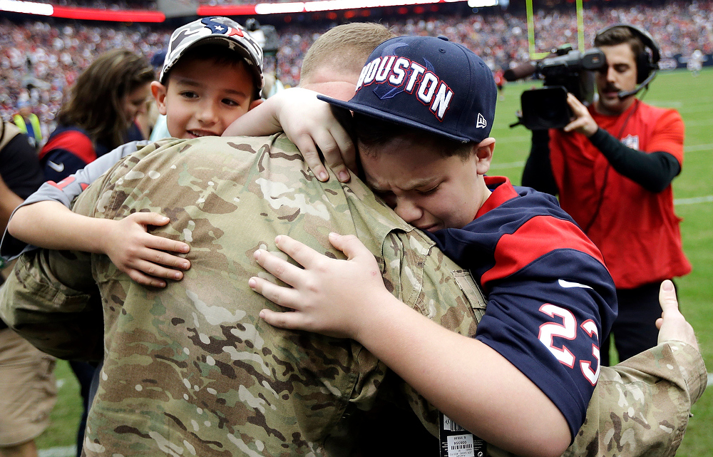 . United States Army Chief Warrant Officer Eric Spoerle, center, is hugged by his sons Tristin, right, and Brandon, left, after surprising his family during halftime at the Indianapolis Colts against the Houston Texans NFL football game on Sunday, Dec. 16, 2012, in Houston. Spoerle surprised his children who did not know he was home from Afghanistan. (AP Photo/Eric Gay)