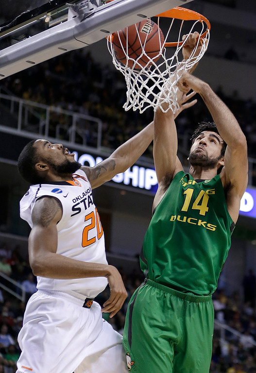 . Oregon forward Arsalan Kazemi (14) dunks over Oklahoma State forward Michael Cobbins (20) during the first half of a second-round game in the NCAA college basketball tournament in San Jose, Calif., Thursday, March 21, 2013. (AP Photo/Ben Margot)