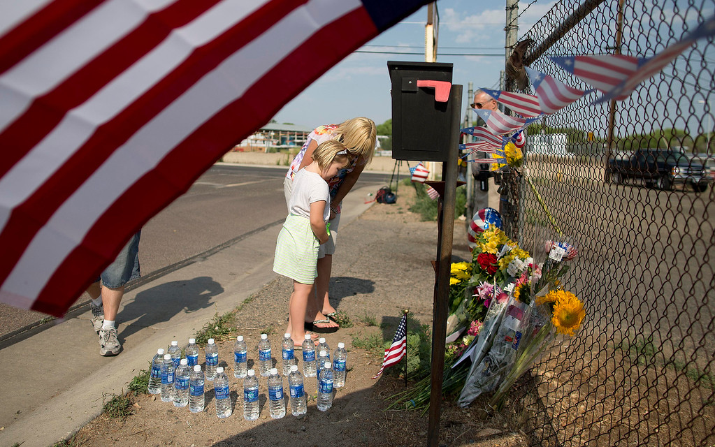. Rhonda Chambers stands at a makeshift memorial of flowers and flags with her daughter Ruby Chambers, 6, outside the Granite Mountain Interagency Hot Shot Crew fire station, Monday, July 1, 2013 in Prescott, Ariz. (AP Photo/Julie Jacobson)