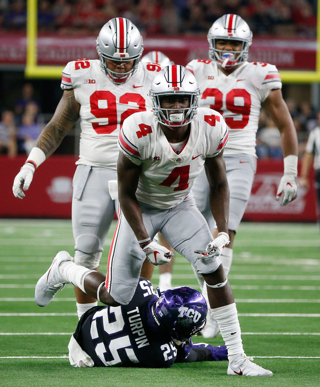 . Ohio State safety Jordan Fuller (4) celebrates a tackle on TCU wide receiver KaVontae Turpin (25) during the second half of an NCAA college football game in Arlington, Texas, Saturday, Sept. 15, 2018. Ohio State won 40-28. (AP Photo/Michael Ainsworth)