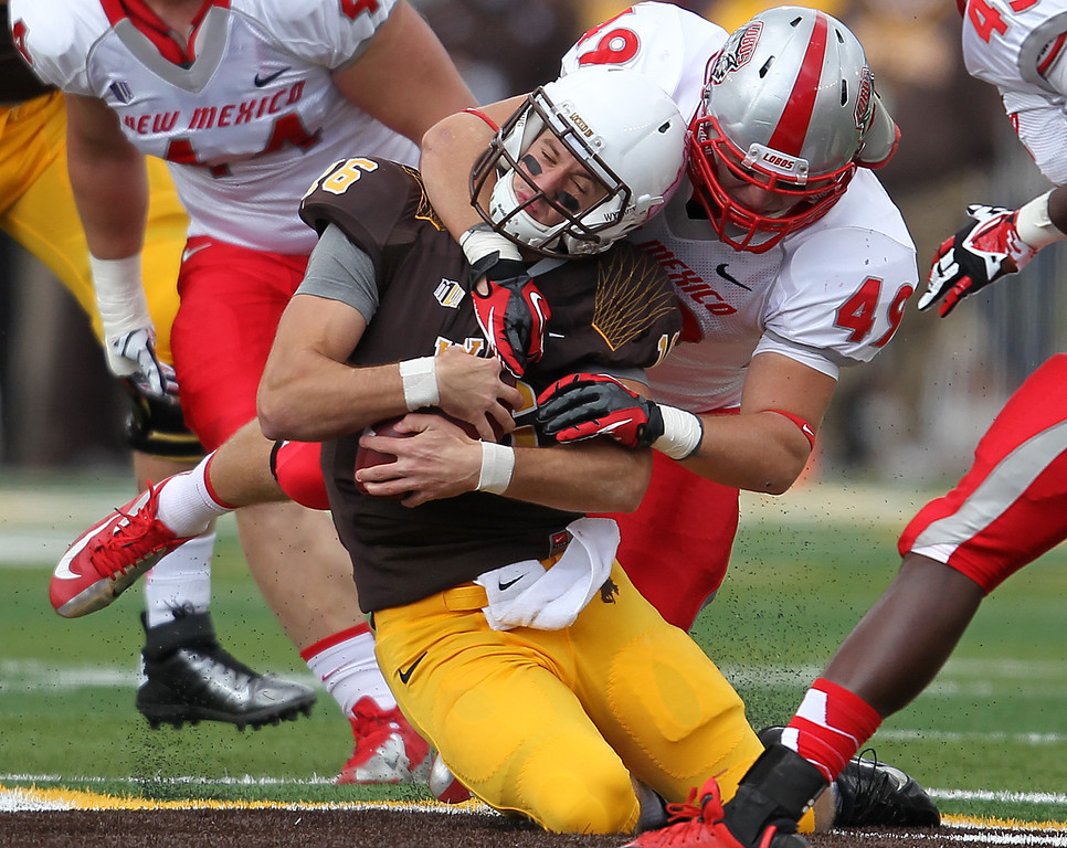 . Wyoming quarterback Brett Smith is brought down by New Mexico linebacker Dakota Cox in the first quarter of an NCAA college football game Saturday, Oct. 12, 2013, at War Memorial Stadium in Laramie, Wyo. (AP Photo/Wyoming Tribune Eagle, Blaine McCartney)