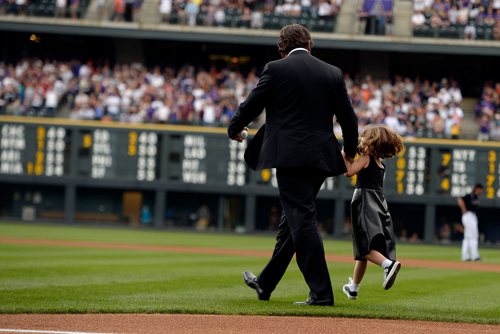 . Colorado Rockies great Todd Helton walks to the mound for the ceremonial first pitch with his daughter, Gentry Grace, during a retirement ceremony for his number 17. Helton, who played 17 season with the Rockies and holds records for many of the organizations career statistics, was honored on Sunday, August 17, 2014. (Photo by AAron Ontiveroz/The Denver Post)