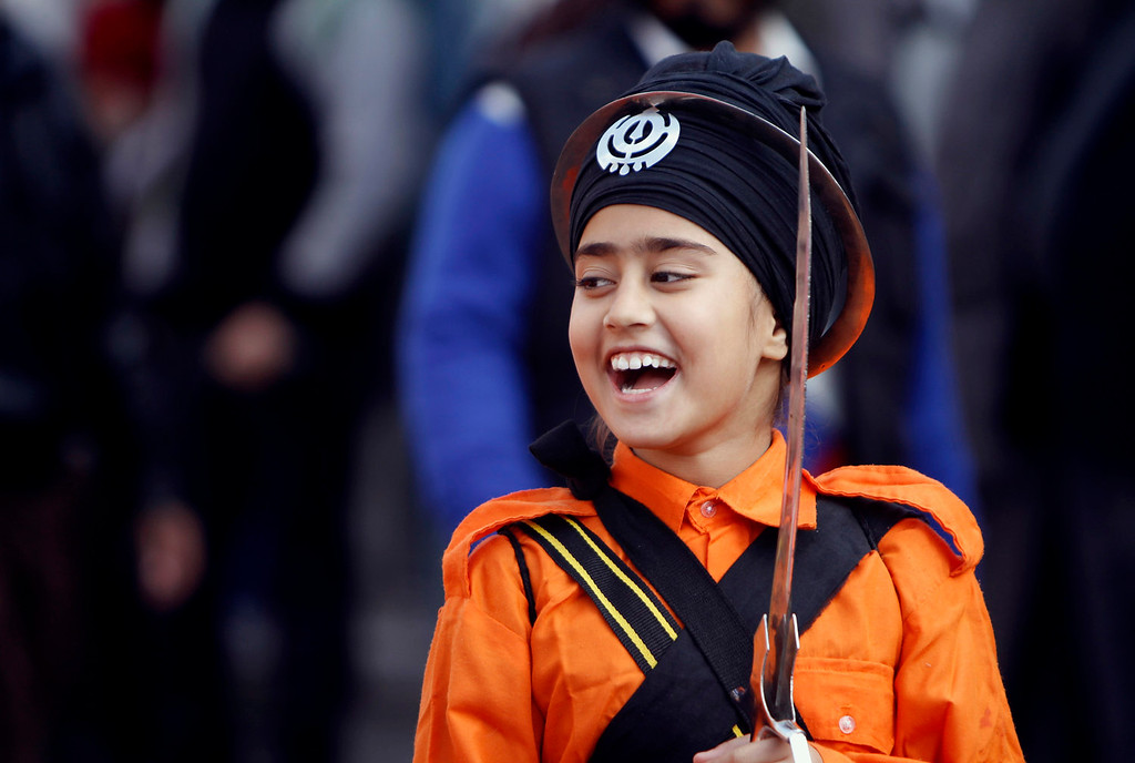 . A young India Sikh girl smiles as she participates in a religious procession ahead of the birth anniversary of Guru Gobind Singh in Jammu, India, Saturday, Jan. 4, 2014. The birth anniversary of Guru Gobind Singh, the tenth Sikh guru, will be marked on Jan. 7 this year. (AP Photo/Channi Anand)