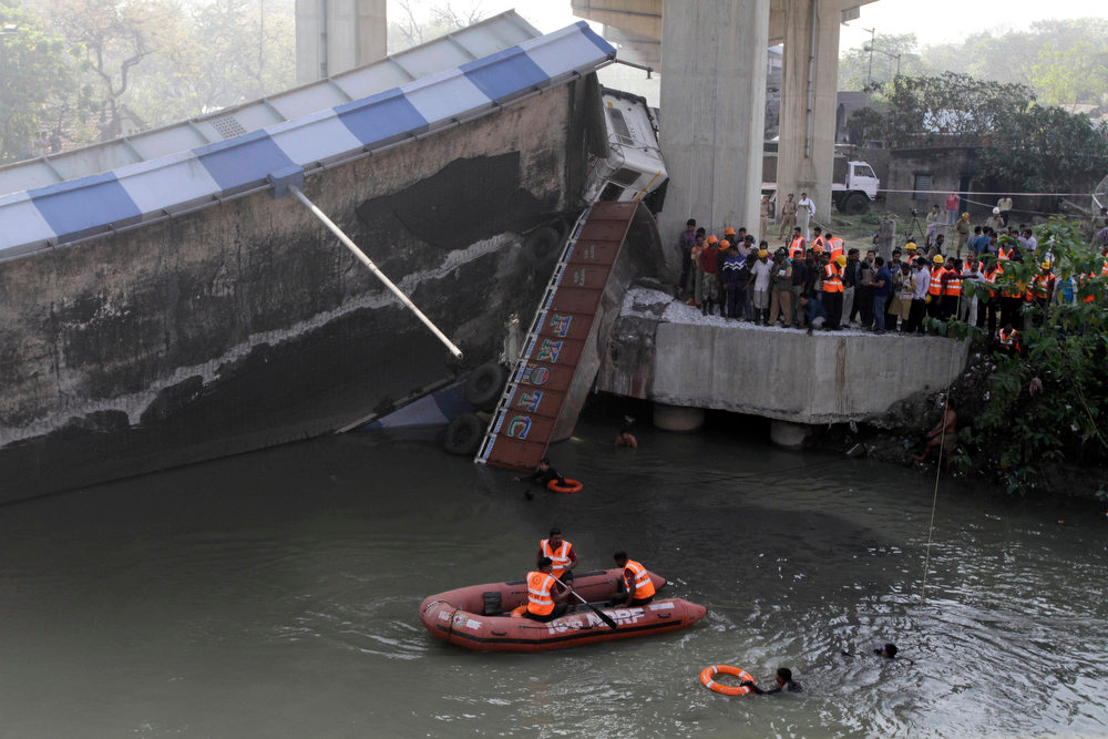 . Rescue workers of the Disaster Management Group conduct search operations at the site where a section of a bridge collapsed early morning in Kolkata, India, Sunday, March 3, 2013. Three persons traveling in a truck that was passing through the bridge were seriously injured in the accident. (AP Photo/Bikas Das)