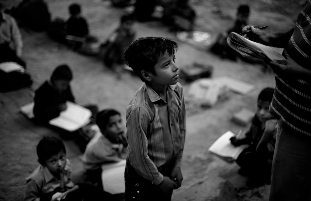 . In this Nov. 7, 2012 photo, underprivileged Indian child Babar Ali, 9, stands as his teacher Laxmi Chandra checks his copy at a free school run under a metro bridge in New Delhi, India. This photo was one in a series of images by Associated Press photographer Altaf Qadri that received an honorable mention in the World Press Photo 2013 photo contest for the Contemporary Issues series category. (AP Photo/Altaf Qadri, File)