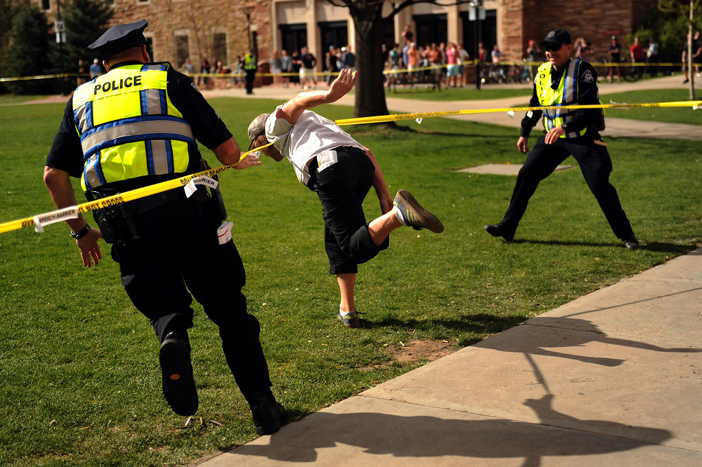 . Officers chase 20 year old Nathan Ryan as he makes a break for the closed the Norlin Quad on Colorado University Boulder campus to crackdown on pro-marijuana protesters on 4-20 at the school in Boulder, Colorado, Friday, April 20, 2012.   Joe Amon, The Denver Post