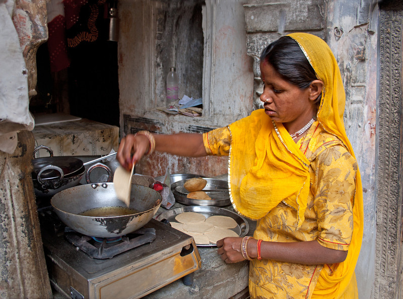 a woman frying bread at home in India
