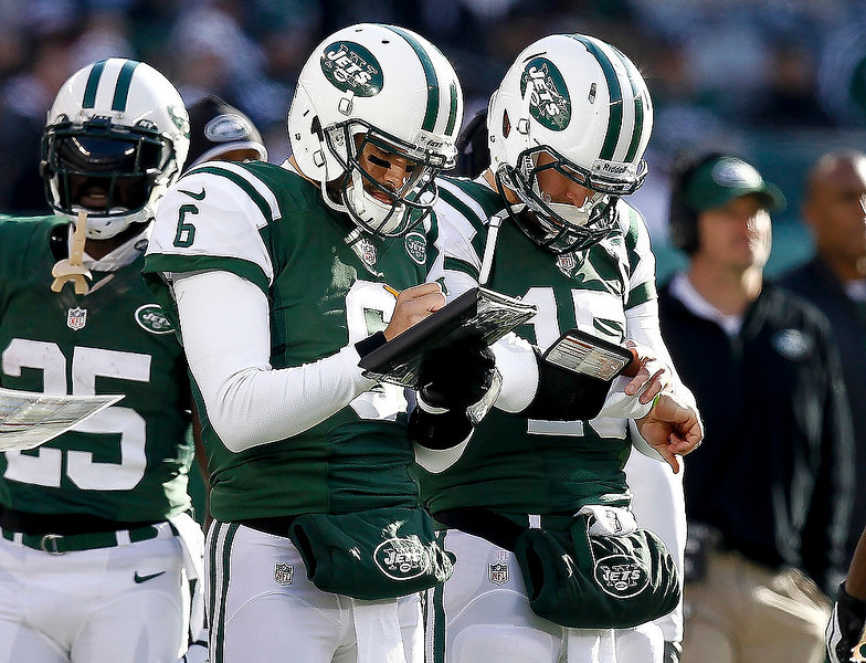 . Mark Sanchez #6 and Tim Tebow #15 of the New York Jets, take notes during their game against the San Diego Chargers at MetLife Stadium on December 23, 2012 in East Rutherford, New Jersey. (Photo by Jeff Zelevansky/Getty Images)