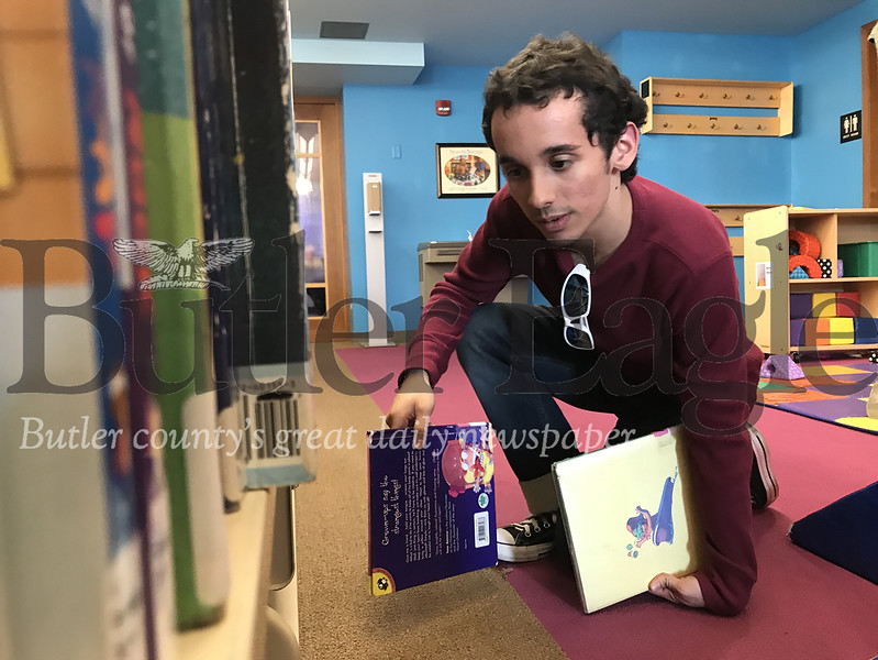 Riley Rios, 18, a senior cyber school student, shelves books at the Butler Area Public Library on Thursday evening during VolunTeen, a drop in volunteer program. Photo by Gabriella Canales.