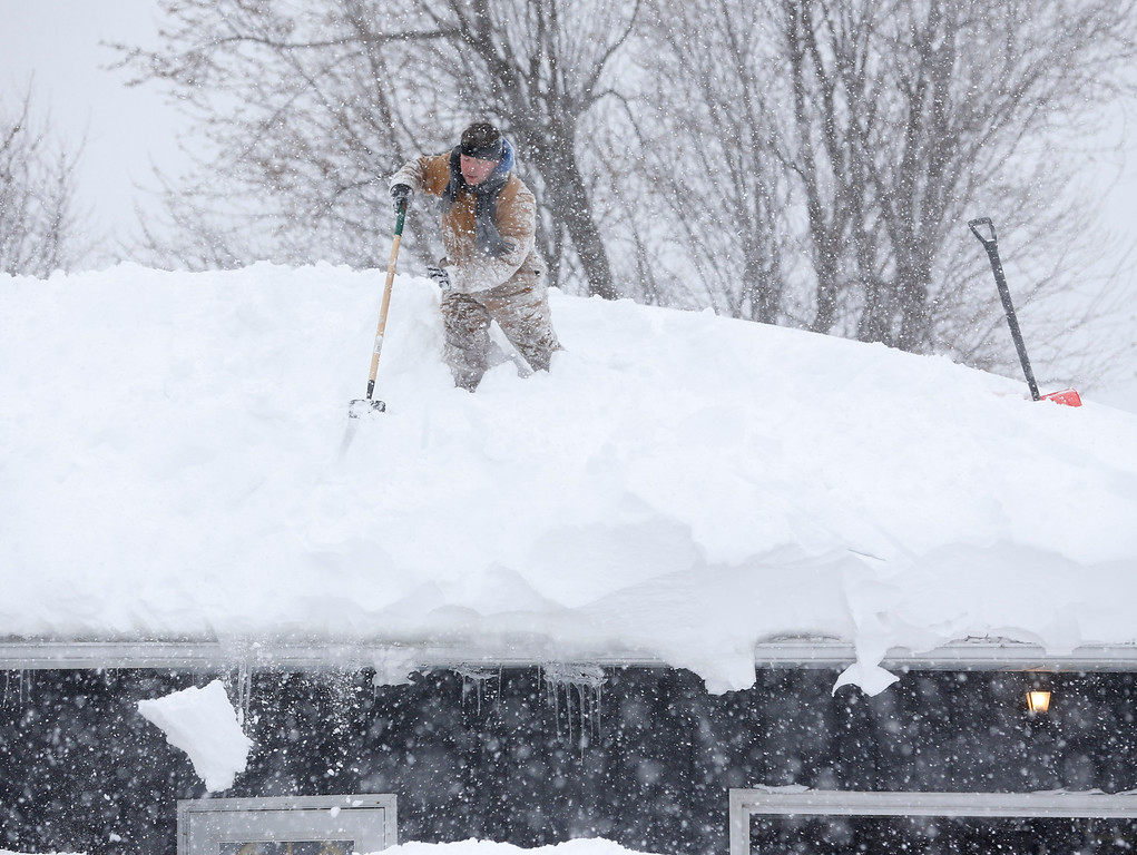 . Tom Mudd clears snow from the roof of his house on Thursday, Nov. 20, 2014, in Cheektowaga, N.Y. A new blast of lake-effect snow pounded Buffalo for a third day piling more misery on a city already buried by an epic, deadly snowfall that could leave some areas with nearly 8 feet of snow on the ground when it\'s all done. (AP Photo/Mike Groll)