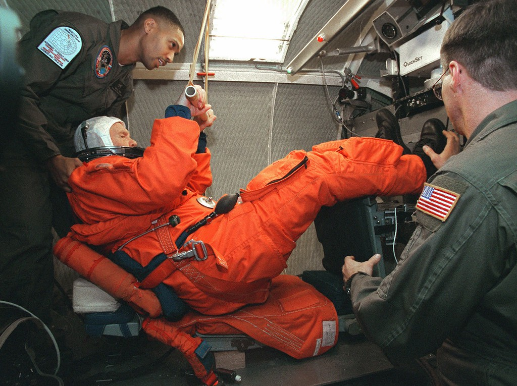 . Sen. John Glenn, D-Ohio, is helped by NASA\'s Carlous Gillis, left, and U.S. Air Force TSgt. Mac Baker, right, as Glenn takes his seat in a space shuttle mid-deck payload seat in a centrifuge, during NASA Space Shuttle training at the Research Laboratory at Brooks Air Force Base, Texas, Thursday, Feb. 19, 1998.  The centrifuge is used by NASA shuttle astronauts to simulate the G-forces astronauts experience during a shuttle launch.  Glenn\'s training in this centrifuge will help to prepare him for his shuttle mission in October. (AP Photo/Kin Man Hui, Pool)