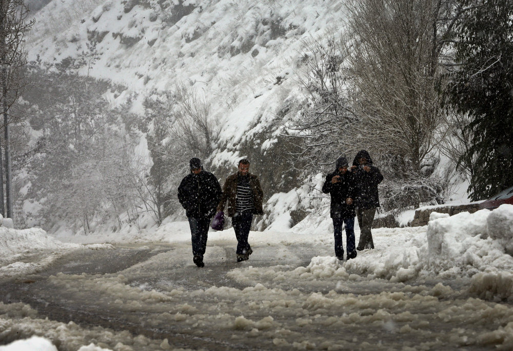 Description of . Lebanese citizens make their way through snow unable to find transport on the Beirut-Damascus highway, in Sawfar mountain, Lebanon, Tuesday Jan. 8, 2013. Lebanon has been hit with a snow storm that has blocked roads in the mountains and brought heavy rain showers to the capital Beirut and other coastal areas since Sunday and according to the Lebanese meteorology, the storm will continue until late Thursday. (AP Photo/Hussein Malla)