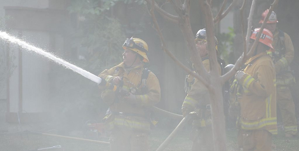 . Los Angeles County Firefighters battle a fire in smoke that damaged a single family home. The fire started in the garage along the 1300 block of Via Verde. No injuries, but 5 cars were destroyed including two jaguars in San Dimas, Calif., on Saturday, Jan.4, 2014. 