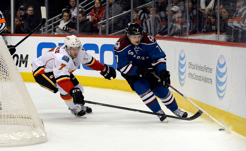 . John Mitchell (7) of the Colorado Avalanche skates the puck behind the Calgary net as T.J. Brodie (7) of the Calgary Flames chases him down during the first period April 8, 2013 at Pepsi Center. (Photo By John Leyba/The Denver Post)
