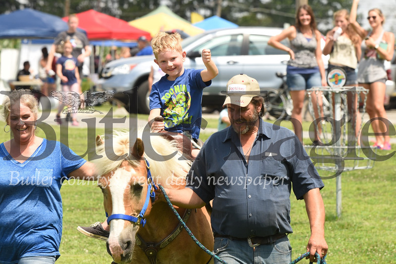 Trenton Hixon,  6, of Renfrew enjoys a free horse ride at Penn Township Community Day courtesy of Paul and Lisa Reichhold of Reichhold Farms. Seb Foltz/Butler Eagle